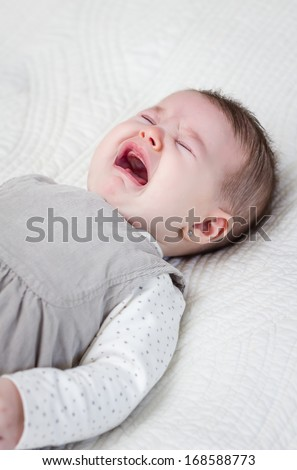 Cute baby girl crying over white bedcover