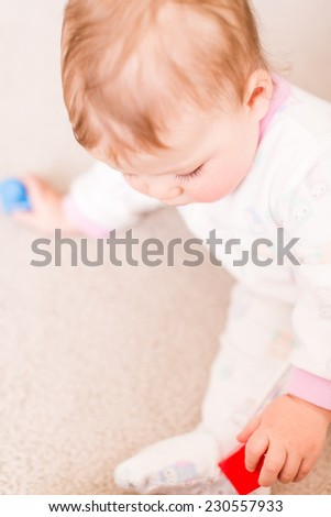 Cute baby girl playing with cubes on the floor.