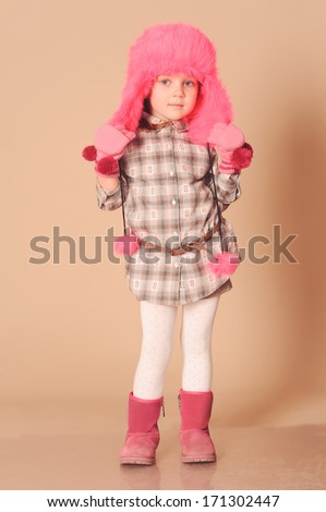 Cute baby girl 4-5 years old wearing trendy stylish winter clothes over beige background