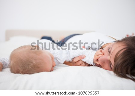 Cute baby placing her hand on the mouth of her mother in a bedroom