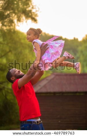 Cute black father and baby girl playing together. Baby flying up in the father's hands
