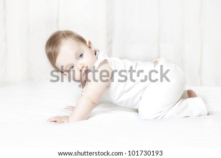 Cute blond baby girl crawls on a bed