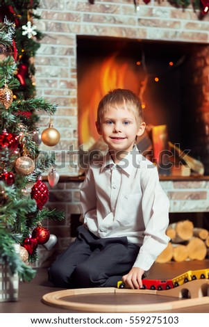 Cute blond boy of 6 years in a white shirt plays with wooden railway, in New Year room near the fireplace and the beautiful large Christmas tree decked out with gold, red and silver toys