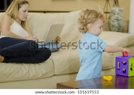 Cute blond boy playing with a puzzle while mom works