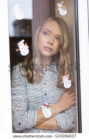 cute blonde woman posing in warm home in winter time behind window bare decorated with small funny snowman stickers. Freckles on visage. Lovely fashion portrait