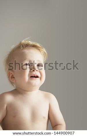 Cute boy crying isolated over gray background