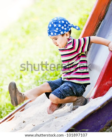 Cute boy in bandana playing on slide