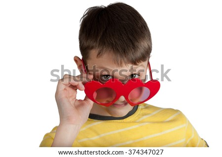 Cute boy in red hearts glasses isolated on white