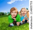 cute brother and his little sister laying on green grass in park - stock photo