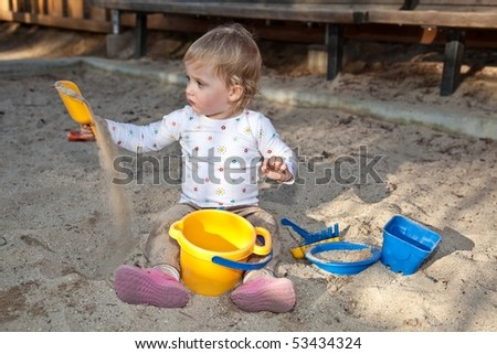 Cute Caucasian baby girl playing with the sand in sandpit.
