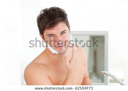 Cute caucasian man ready to shave in the bathroom at home