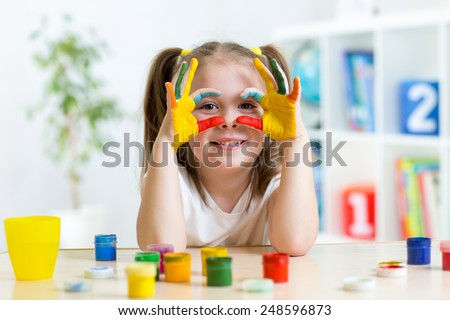 cute cheerful kid girl showing her hands painted in bright colors
