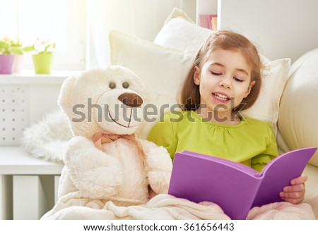 cute child girl reading a book at home. self learning. home study