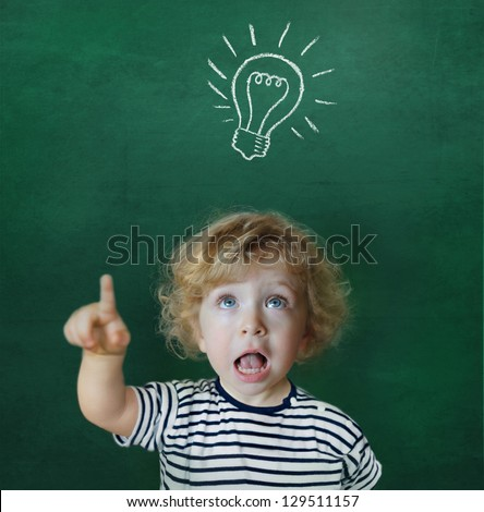 Cute child in front of a green chalkboard showing up to a light bulb