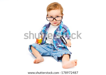 Cute child in glasses with a magnifying glass is experimenting with apple isolated on white background