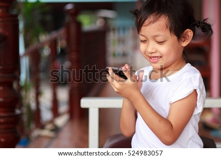 Cute child little girl playing smartphone with happy at home.