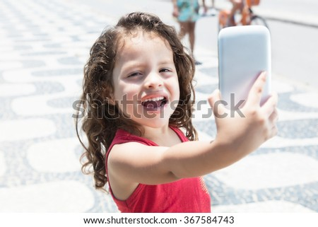 Cute child taking photo with mobile phone