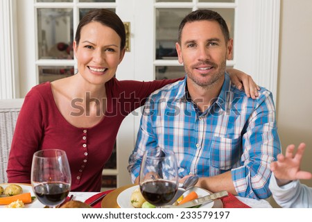 Cute couple smiling at camera at home in the living room