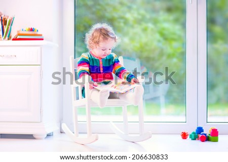 Cute curly little girl, funny toddler wearing a warm colorful knitted dress reading a book relaxing in a white rocking chair next to a big garden view window at home or daycare center