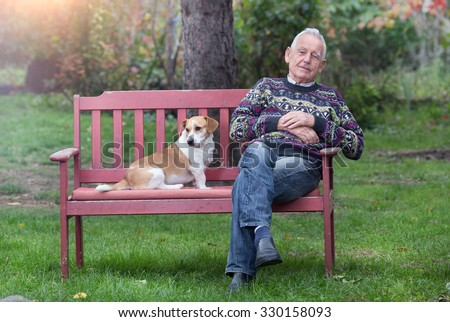 Cute dog sitting next to his senior owner on bench in garden