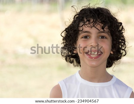 Cute eight years old Hispanic boy smiling with shallow depth of field in the countryside