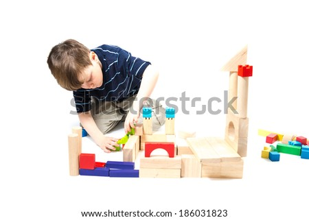 Cute elementary school boy build block construction on white background