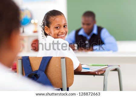 cute elementary schoolgirl in classroom with classmate and teacher