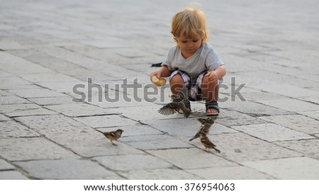 Cute fair-haired blond kid tiny little child baby boy feeding sparrows with bun sitting on haunches on flag-stone pavement cityscape on blurred grey background, horizontal picture