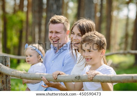 Cute family portrait of four people mother father son daughter park near forrest