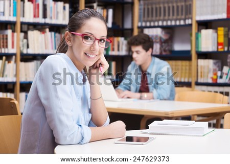 Cute female student with glasses studying at the library