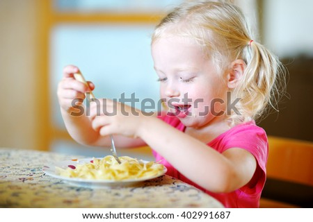 Cute funny little girl eating spaghetti at home