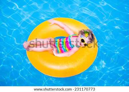 Cute funny little toddler girl in a colorful swimming suit and sun glasses relaxing on an inflatable toy ring floating in a pool having fun during summer vacation in a tropical resort