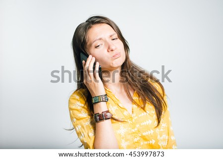 cute girl displeased talking on phone, studio isolated