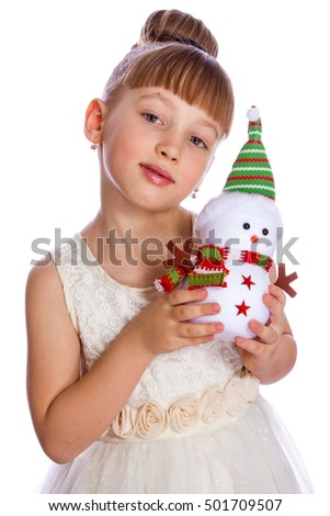 Cute girl holding a toy snowman in a bright dress on a white background