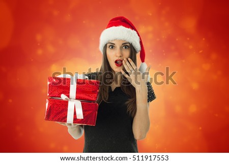 Cute girl in santa hat with red gift box in hands looking at the camera and smiling on red background