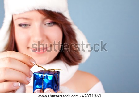 cute girl in white opening a present - focus on the present