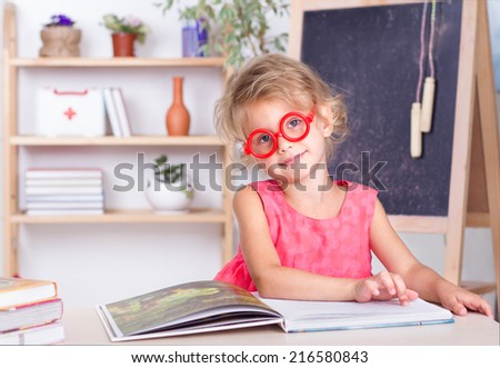 Cute girl reading a book at the table