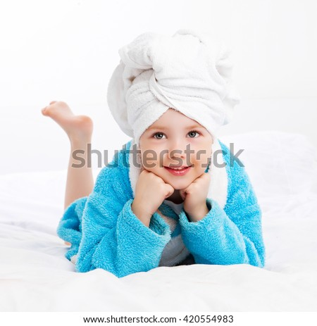 cute girl wearing a bathrobe and a towel after shower in bed at home