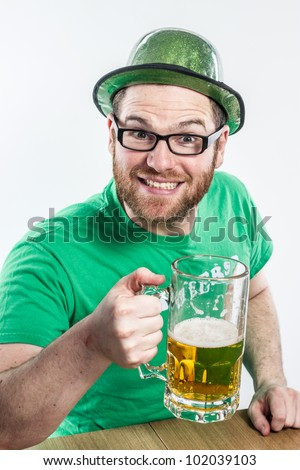Cute glasses Irish man in green shirt St. Patty's Day pub drinking large glass mug of beer to Ireland