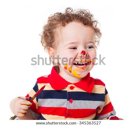 Cute happy baby boy kid child playing and painting with his face covered with spots of bright paints isolated on white background studio portrait