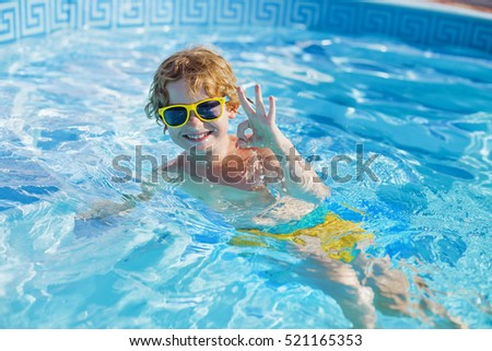 Cute happy blond child with yellow glasses swimming and splashing in water. Little boy spends his holidays in the pool.