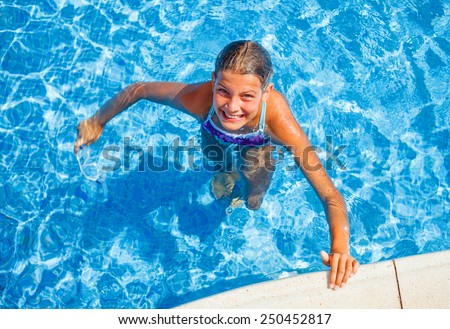 Cute happy young girl swimming and snorking in the swimming pool