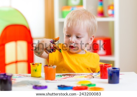 cute kid boy painting at home or playschool