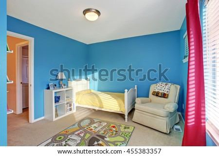 Cute kids room with blue walls, carpet and red curtains