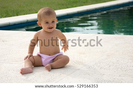cute little baby eats strawberries by the pool
