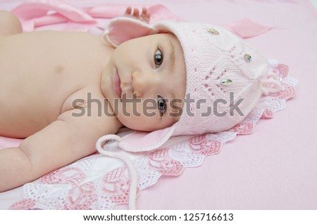 Cute little baby in an amusing pink hat