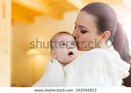 Cute little baby in the arms of her mother in their living room.
