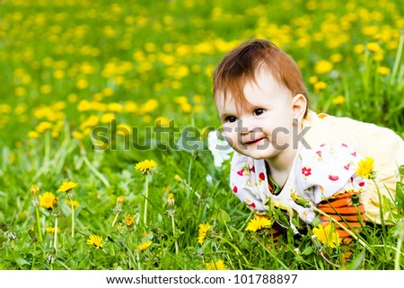 Cute little baby on the dandelion meadow