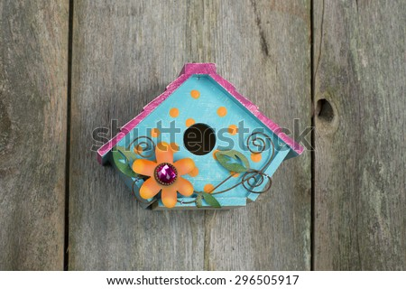 Cute little blue, yellow and pink birdhouse with orange flower and vines hanging on a rustic old wooden fence