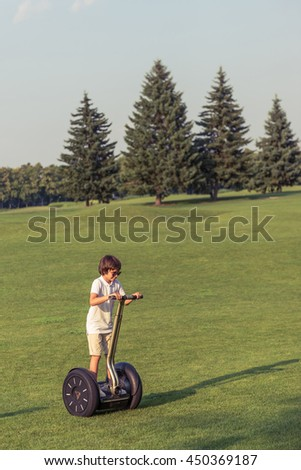 Cute little boy in casual clothes and sun glasses is riding a segway in the park